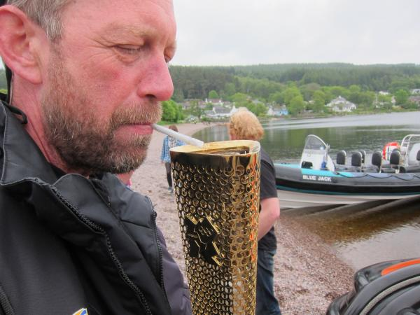 Lighting fag with olympic torch after delivery on Lochness leg of torch tour